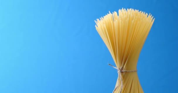 Bundle tied with string spaghetti dry pasta slowly rotates.