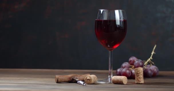 Sklenice červeného vína a hroznů se pomalu otáčí na stole.