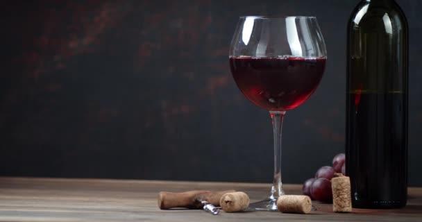 Rotwein in der Flasche und im Glas langsam auf dem Tisch drehen.