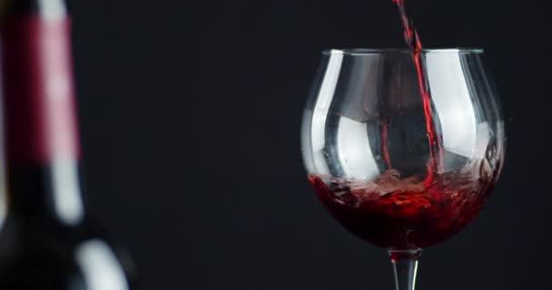 V nalévání sklenice červeného vína se vzduchovými bublinami a cákanci.