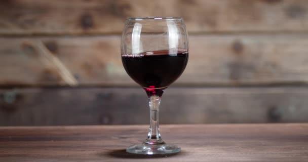 Ein Glas Rotwein steht auf einem Holztisch.