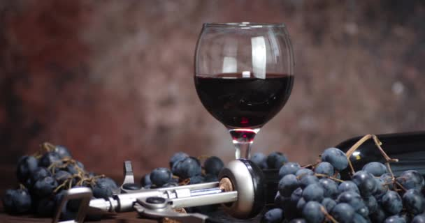Glass of red wine and grapes on the table slowly rotating.