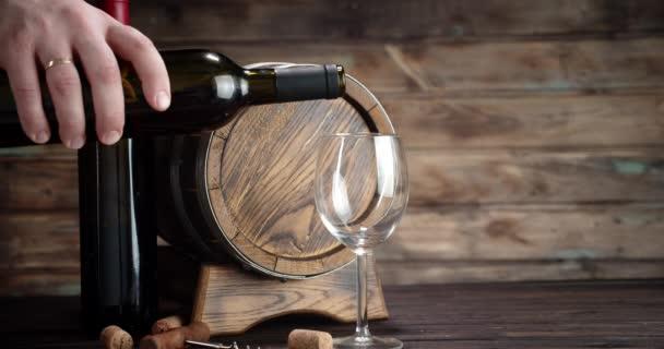 Mužská ruka nalévá červené víno z láhve do skla.