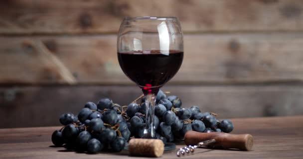 Rotwein im Glas und frische Trauben rotieren langsam.