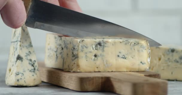 Male hand with a knife cut off a piece of brie cheese.