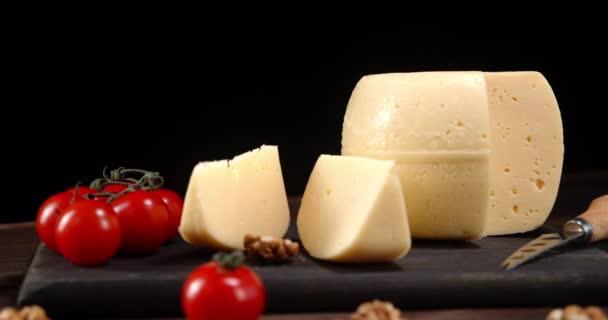 Sýr s rajčaty na řezací desce se pomalu otáčí.