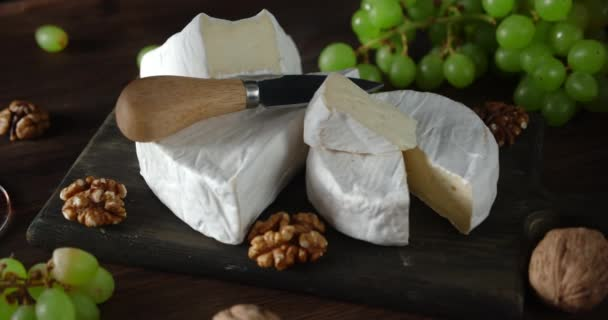 Sýr Camembert s hrozny a vlašskými ořechy se pomalu otáčí.