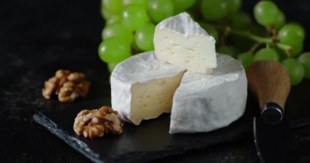Sýr Camembert na kamenné desce se pomalu otáčí.