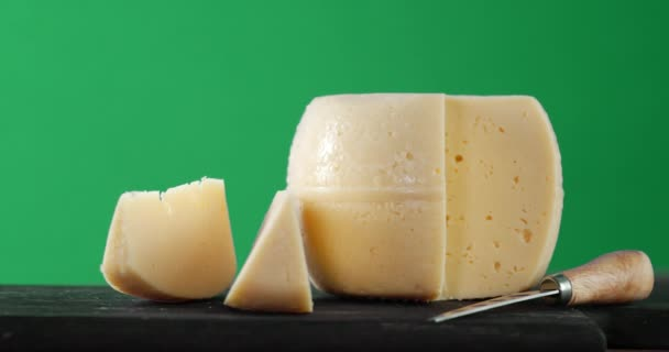 Kousky sýra s nožem na stole se pomalu otáčejí.