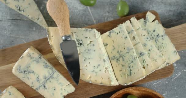 Krájený sýr s olivami se pomalu otáčí.