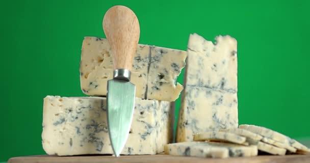 Kousky sýra na stole s nožem se pomalu otáčejí.