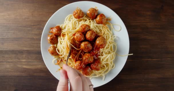 Male hand with a fork mixing the meatballs with spaghetti.