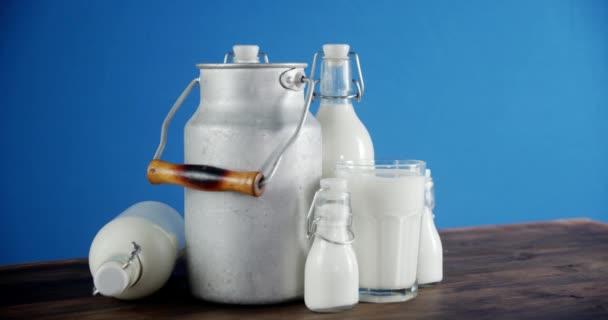Mléko v lahvích, sklo a plechovky na stole se pomalu otáčí.