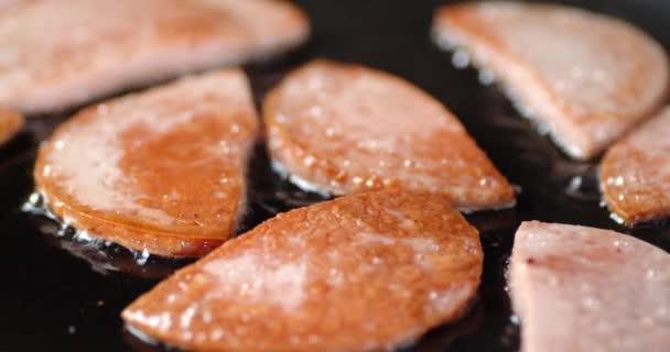 A kolbászdarabokat olajban sütik egy serpenyőben..