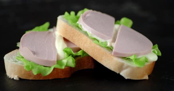 A főtt kolbászszeleteket tartalmazó szendvicsek lassan forognak..