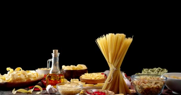 A variety of types of pasta dry on table slowly rotates.
