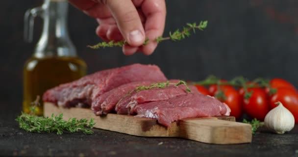 Die Hand des Mannes legt Thymian auf rohes Rindfleisch.