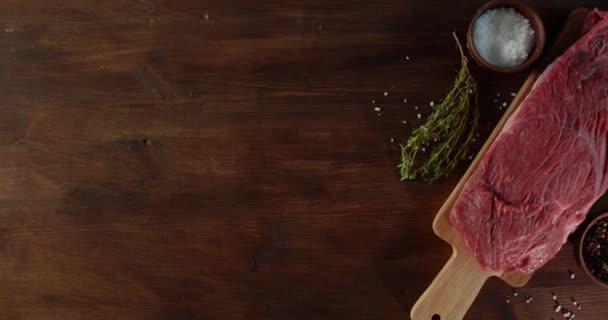 Kousek čerstvého syrového hovězího na řezací desce.