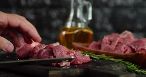 Stücke rohes Rindfleisch werden auf einen Teller gelegt.
