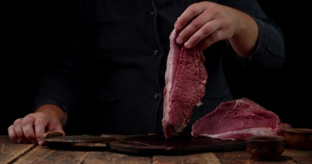 Mens hands hold a piece of raw beef.