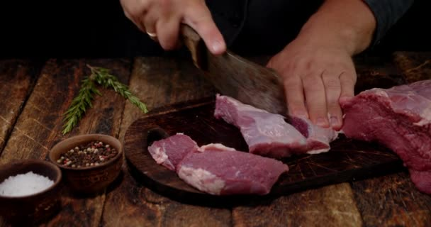 Hovězí maso se krájí na kusy na řezací desce.