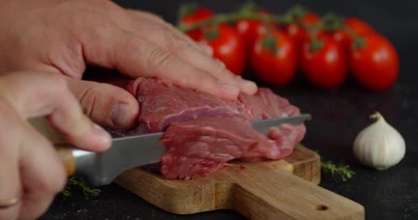 Männerhände schneiden Rindfleisch in Stücke.