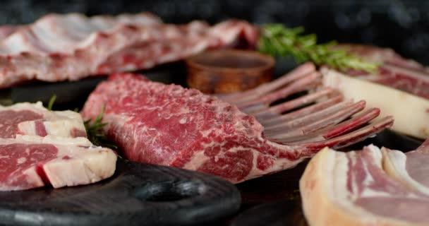 Mužská ruka dává rozmarýn na různé syrové maso.