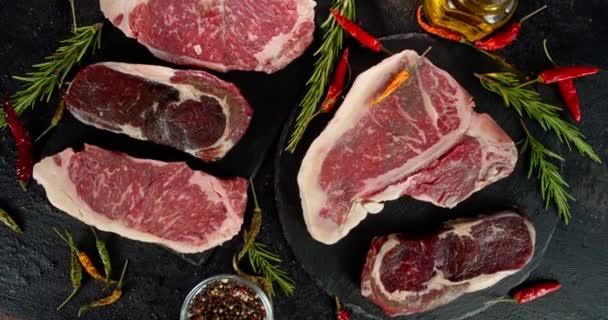 Verschiedene Arten von rohem Rindfleisch mit Rosmarin rotieren langsam.