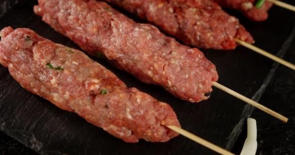 Syrové kebab párky na klacku na kamenné desce.