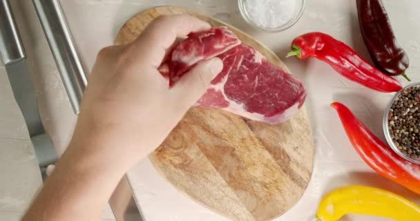 Egy férfi keze nyers marhahúst tesz a vágódeszkára..