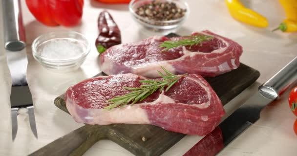 Steak raw beef ribeye s rozmarýnem na desce otáčí.