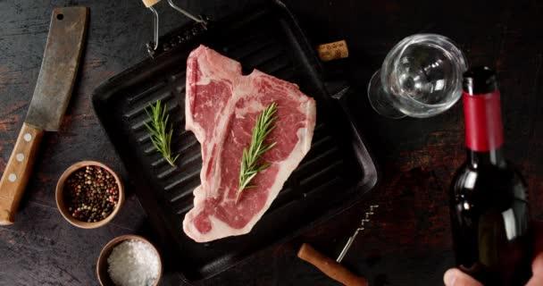 Steak raw beef t-bone v pánvi na smažení se sklenicí vína.