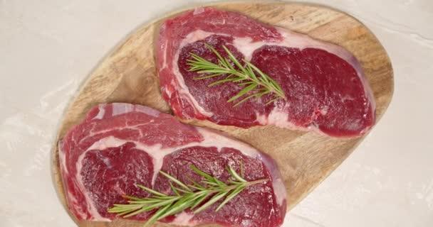 Roh-Rindfleisch-Ribeye-Steak mit Rosmarin rotiert auf einem Brett.