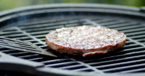 Stěrka otočí hamburger na grilu s kouřem.
