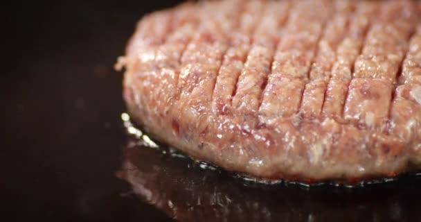 Syrové maso z hamburgerů se smaží párou na pánvi.