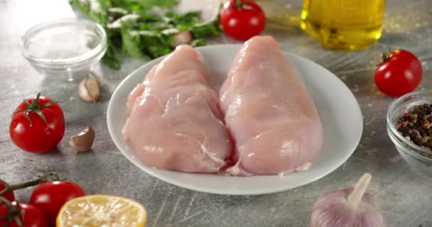 Raw chicken fillet with tomatoes and lemon rotates on table.