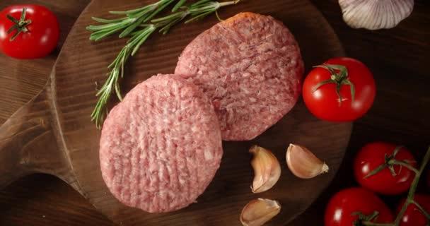 Roher Burger mit Knoblauch, Rosmarin und Tomaten rotiert.