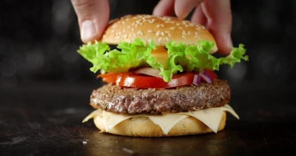 Mužská ruka položí na hamburger buchtu..
