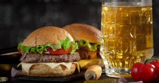 Burger a sklenici piva na stole.
