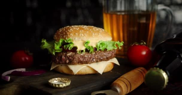 Vynikající burger a sklenice piva na stole se otáčejí.