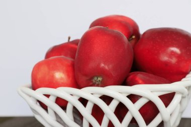 Large red apples from the home garden lie in a white wicker ceramic in a vase on a white background