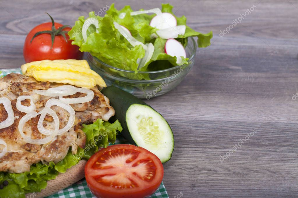 Preparing delicious homemade chicken burger with fries, fresh lettuce, tomatoes and cucumbers  on a wooden background. Fast food - lunch. With an empty space for your text. View from above.Copy space.