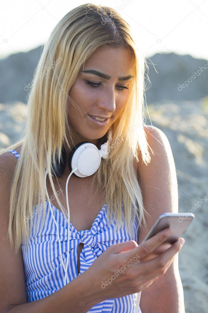 Young pretty girl in a dress sits on a sandy beach and using a mobile phone. Texting mesages