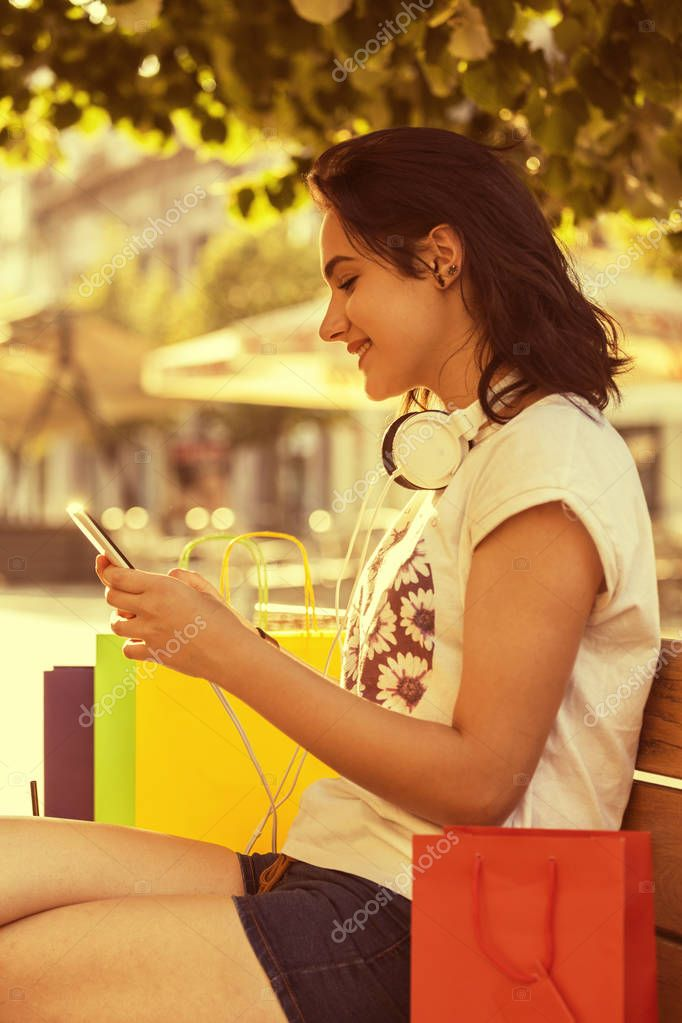 Young beautiful smiling girl, a teenager, with a headphones resting on the bench after shopping. Next to her are full bags, things she bought. She holds a mobile phone in her hand and texting message