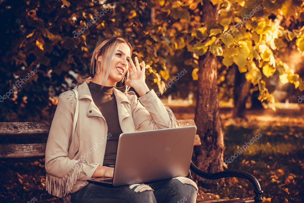 Girl working at a laptop in the park, sitting on a bench outdoors. Sunny autumn day in the park. Wireless Internet, remote work, freelance, prints a message, communicate in social networks.