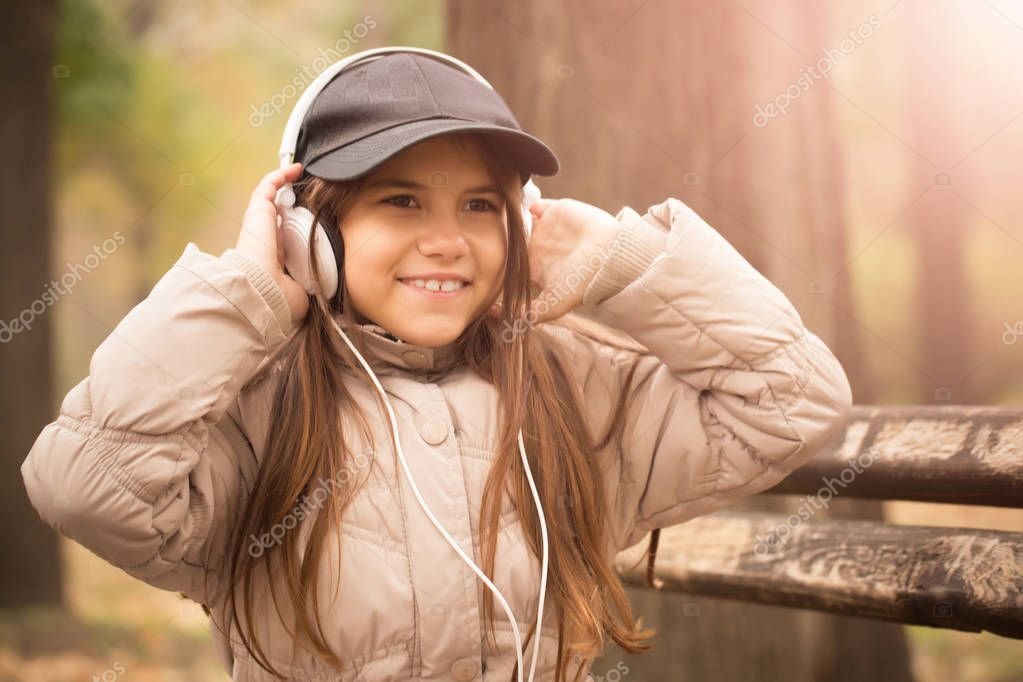 Child girl sitting on a bench in the park and listening to music on headphones.High ISO