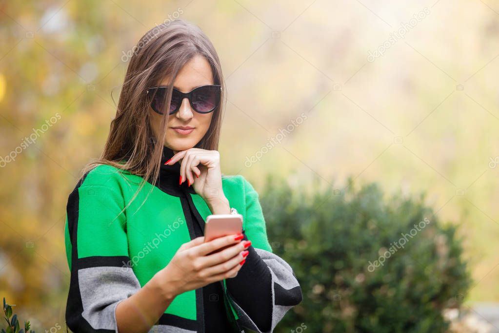 Beautiful woman using  mobile phone in the park. Texting message. Copy space