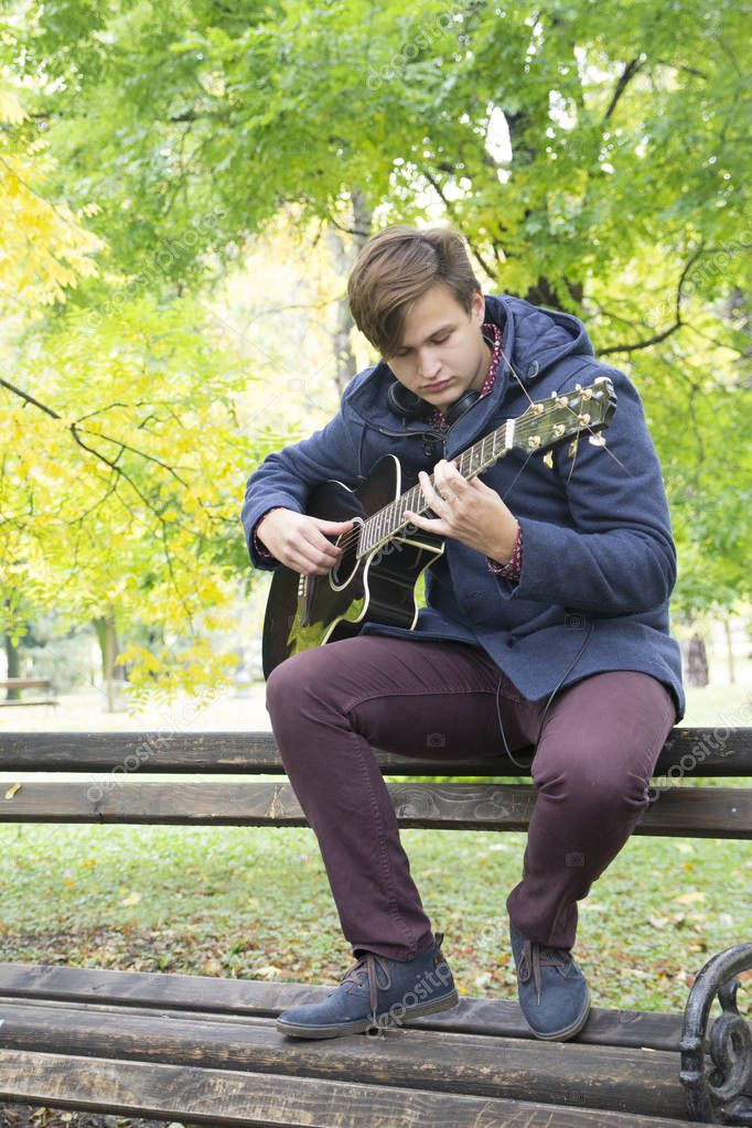 Young man with an acoustic guitar, Selective focus and small depth of field, lens flare