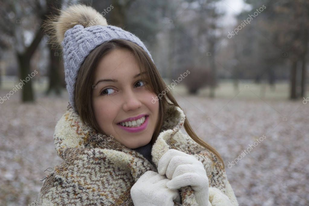 Young girl with a warm cap and scarf walking