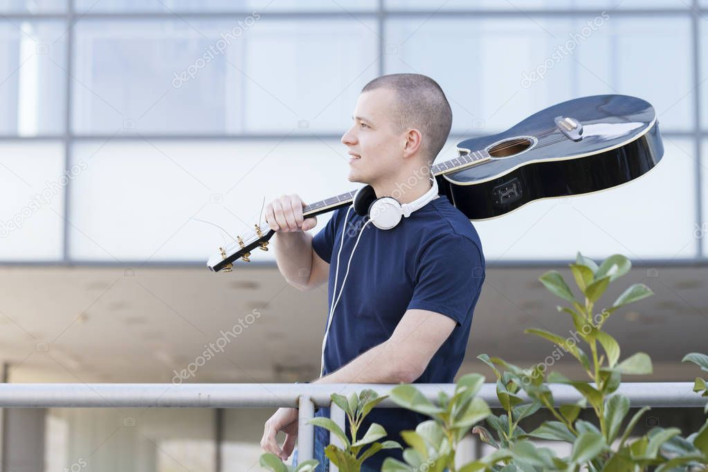 Handsome young man enjoying the outdoors with a guitar.Selective focus and small depth of field.